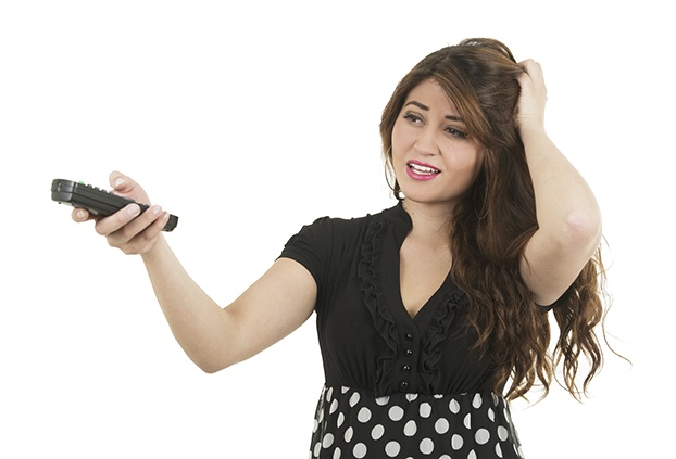 young hispanic woman holding remote control looking confused