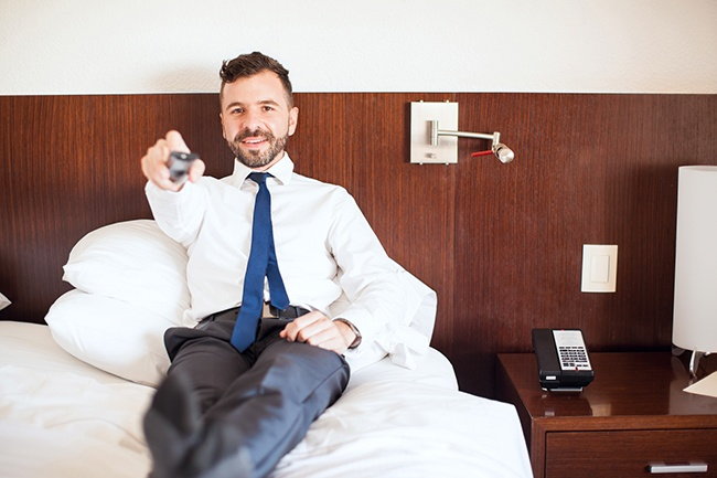 Portrait of a handsome Hispanic businessman relaxing in his hotel room and watching TV during a business trip