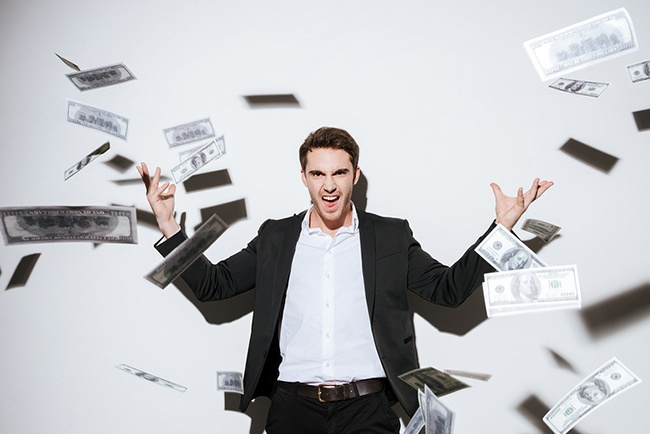 Picture of handsome businessman looking at camera while throws away money.
